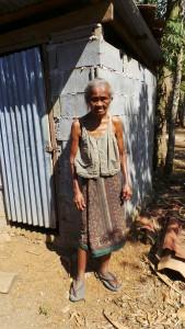 Eine Frau steht vor einer mit grauen Steinen gemauerte Toilette, welche mit einer Wellblechtür verschlossen ist.