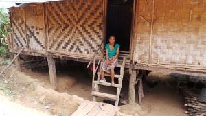 Frau On sitzt vor ihrer hochstämmige Wohnung. Die wände sind ein Geflecht aus Palmzweigen.