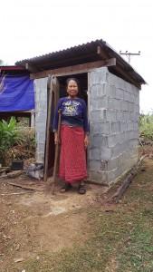 Gestützt auf eine Gehhilfe steht Frau Me Tau Ta vor einer gut aufgebauten Toilette.