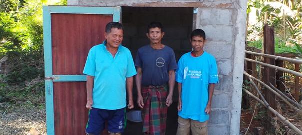 Herr Si steht mit den Bauleuten vor seiner neuen Toilette. Er strahlt vor Freude.