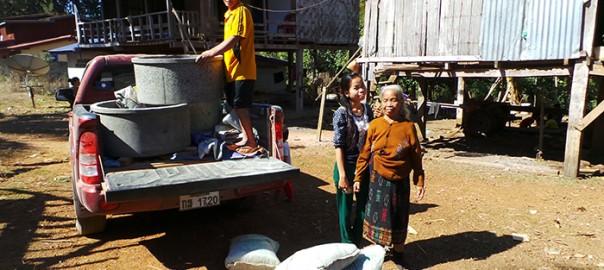 Auf einem roten Transporter werden 3 große Betonringe im Dorf abgeladen.
