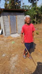 Herr Sunn hat seine Augen verschlossen. Er trägt ein rotes T-Shirt und tastet sich mit einem Stock zurückkehrend von der Toilette zum Haus zurück.