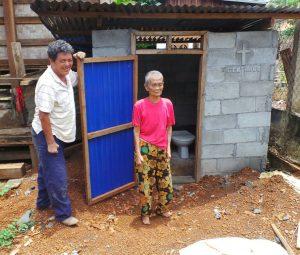 Frau Tau Lah aus Ban Nam Sai thouang steht mit dem Baumeister neben ihrer neuen Toilette
