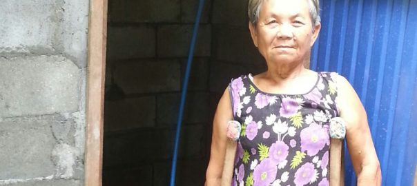 Frau Gong steht gestützt auf Gehhilfen vor ihrer neuen Toilette
