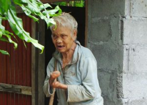 Frau Tau Tum steht auf einen Stock gestützt vor ihrer Toilette