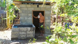 Herr Song steht in der Tür seiner neuen Toilette