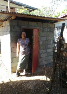 Frau Luang steht in der Tür ihrer Toilette