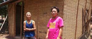 Eine helle geflochtene Wand aus Bambusblättern ziert das neue Haus. Herr Kham steht mit einem roten Hemd vor dem Haus. Seine Frau steht im Hintergrund.