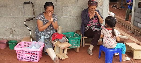 Zwei Frauen sitzen vor einem gemauerten Haus und beschäftigen sich mit Handarbeit. Ein junges Mädchen schaut zu.