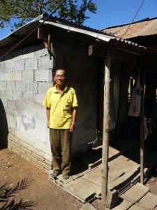 Ein leprakranker Mann steht vor einer gemauerten Hütte mit einem Dach aus Wellblech.