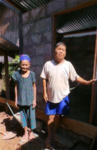 Herr und Frau Phia Xiong stehen vor einer gemauerten Toilette. Der Türrahmen aus Holz und das Wellblechdach sind fertig.