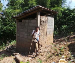 Herr Kham Dee ist lehnt sich mit seinem Rücken gegen eine Ecke der Toilette.