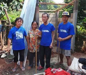 Herr Tong je Va steht mit einer Frau und 2 Bauerabeitern vor seiner im Rohbau befindlichen Toilette. Die Männer tragen ein blaue T-Shirt.