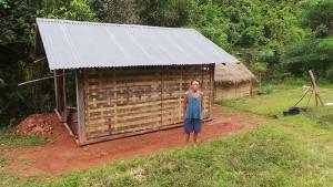 Herr Ya Ning Vangsteht vor seiner neuen Hütte. Sie besteht aus einer Holzkonstruktion, die mit Pastmatten verkleidet ist. Ein Wellblech schützt sie vor Regen.