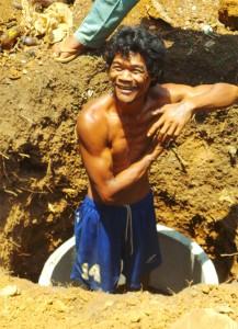 Ein junger gesunder kräftiger Mann steht in einem Erdloch und freut sich.