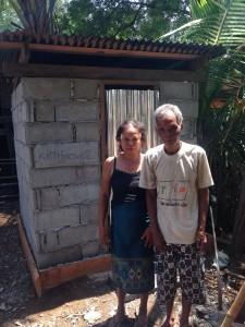Die neugebaute Toilette ist gemauert und mit einem Holzdach mit Wellblech gebaut. Herr und Frau Ter stehen vor der Tür aus Wellblech.