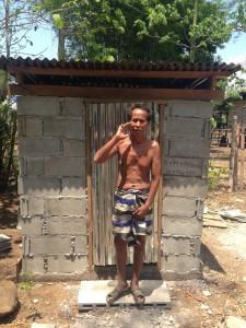 Herr Thon steht in Badebekleidung vor seiner neuen Toilette. Man sieh in seinen Badeschuhen nur die großen Zehe.