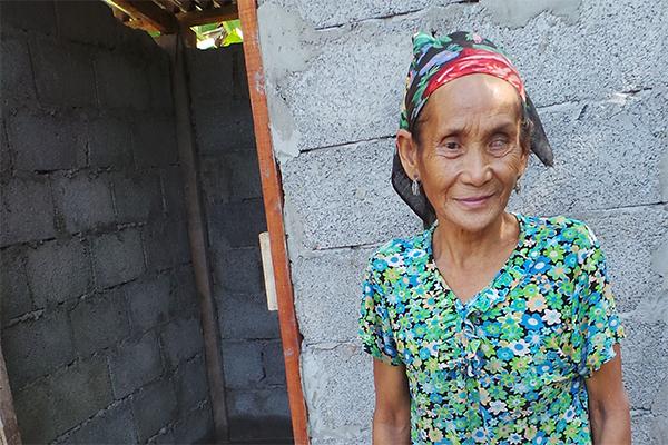 Frau Me Tau Sai Phia steht vor ihrer gerade fertig gewordenen Toilette. Der Beton am Fußboden und die Stufe vorm Eingang sind noch ganz frisch.