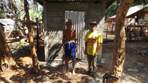 Unter Palmen ist eine neue Toilette gemauert worden. Der Besitzer und der Erbauer stehen vor ihr. Eine silberne Wellblechtür glänzt in der Sonne.