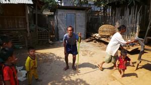 Herr Phan Gan steht gegrümmt und auf einen Stock gestützt vor seiner Toilette. Die Kinder und Mutter spielen auf dem Hof.