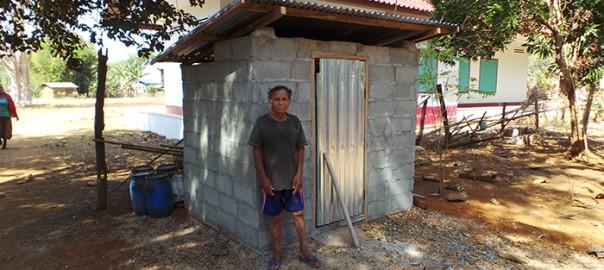 Herr Sufi steht vor seiner Toilette. Im Hintergrund ist ein modernes Haus mit grünen Fensterläden zu sehen.