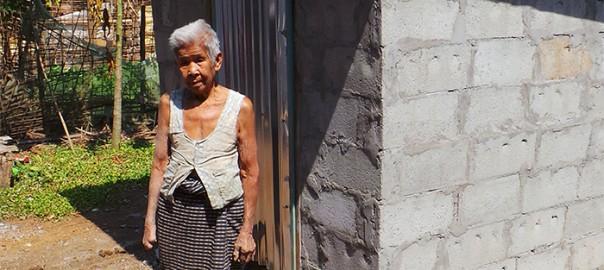 Frau Tau Chan steht vor ihrer Toilette und schaut uns an.
