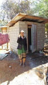 Frau Tau Pan steht vor ihrer geöffneten Toilette und hebt zum Gruß ihre rechte Hand.