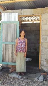 Frau Tau Phüa steht vor ihrer Toilette und schaut uns mit dem rechten Auge an. Ihr linkes Auge ist geschlossen.