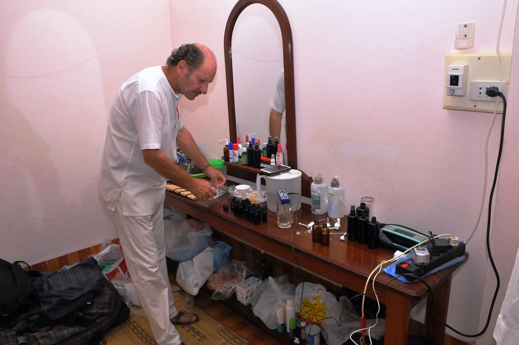 MissionarHubert Kastner steht in seinem Labor vor einem Tisch mit vielen Flaschen und Geräten.