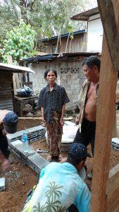 Frau Tau Biu steht mit dem Baumeister auf dem Bauplatz. Die Klärgrube und das Fundament sind fertig.