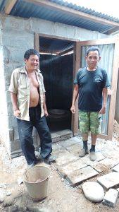 Po Mon und der Baumeister stehen vor der neuen Toilette.