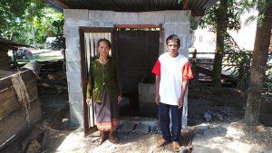 Frau Tau Lanh und der Dorfälteste stehen vor den neu errichteten Toilette.