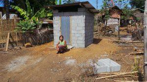 Frau Tau Daeng sitzt vor ihrer neuen Toilette.