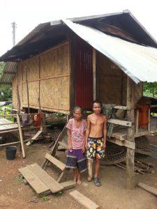 Frau Tau Mem steht mit ihrem Besuch vor dem neu aufgebautem Haus